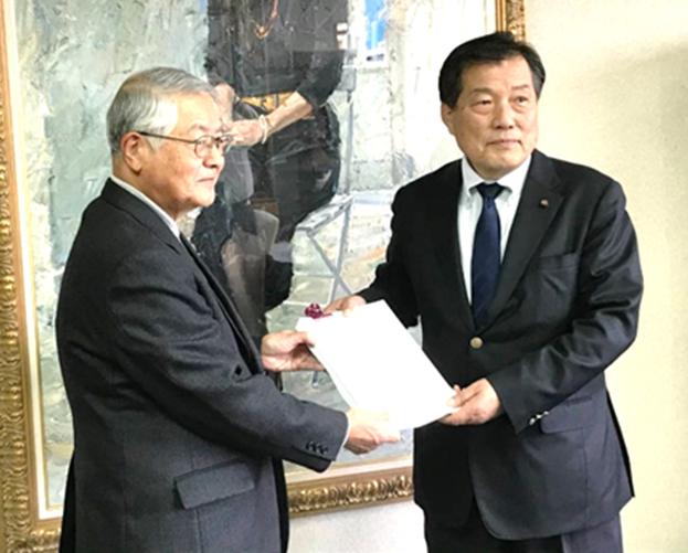 山本市議会議長(右)に署名を手渡す会の代表(左)